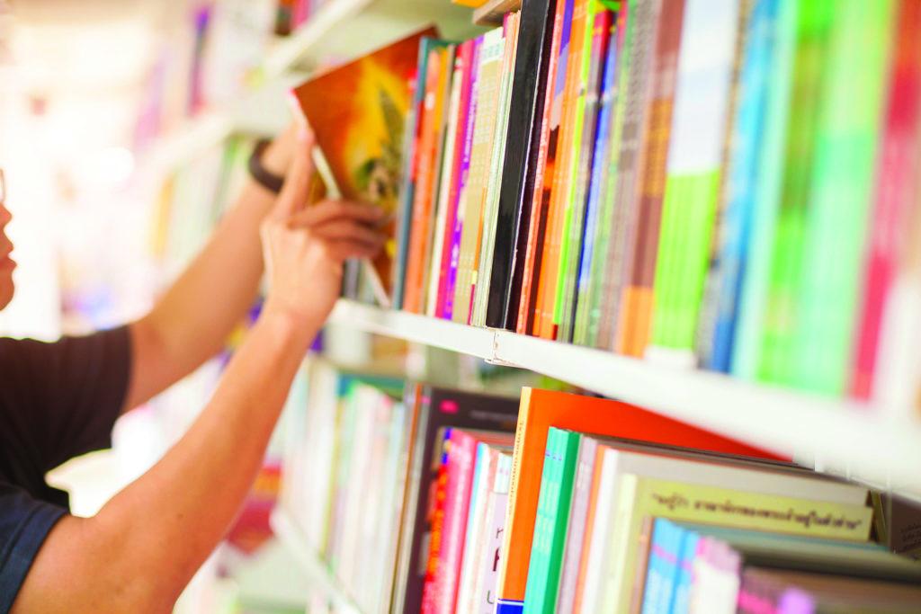 main dans une bibliothèque prenant un livre